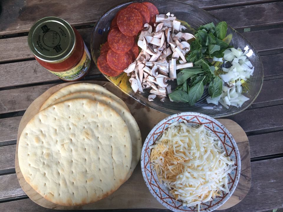 Pizza ingredients for a kid friendly camping dinner experience.