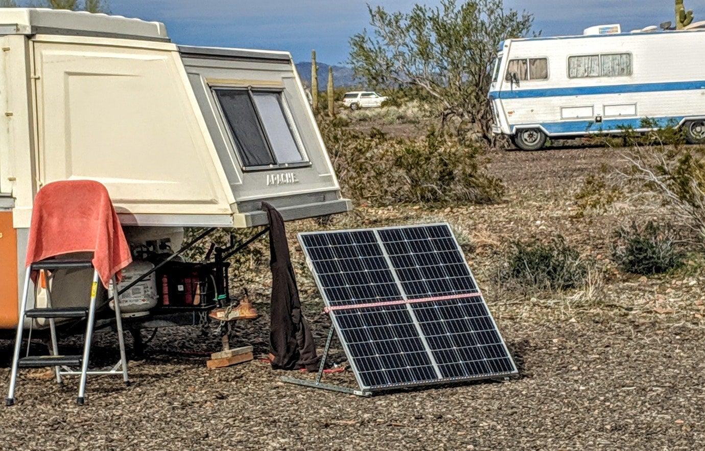 solar panel resting on gravel ground beside pop out trailer