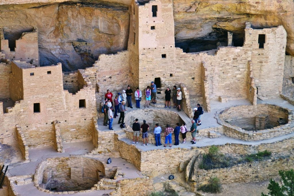 visitors gather around mesa verde cliff dwelling