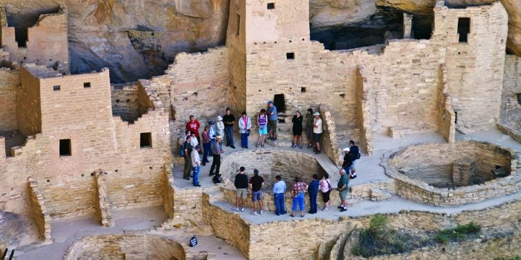 visitors gather around ancient mesa verde cliff dwellings