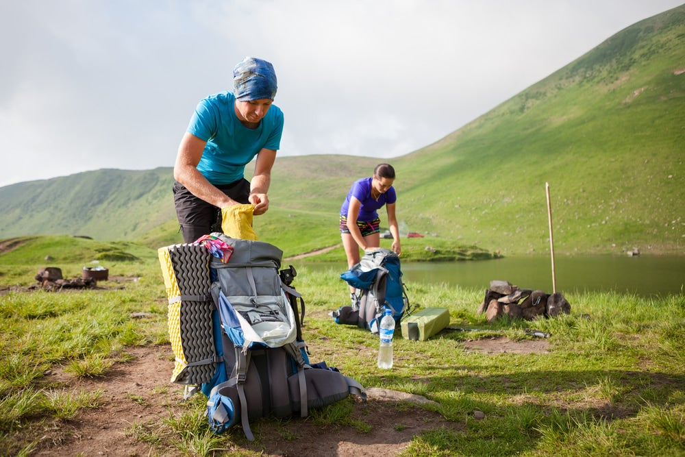 two hikers pack their bags at the campsite