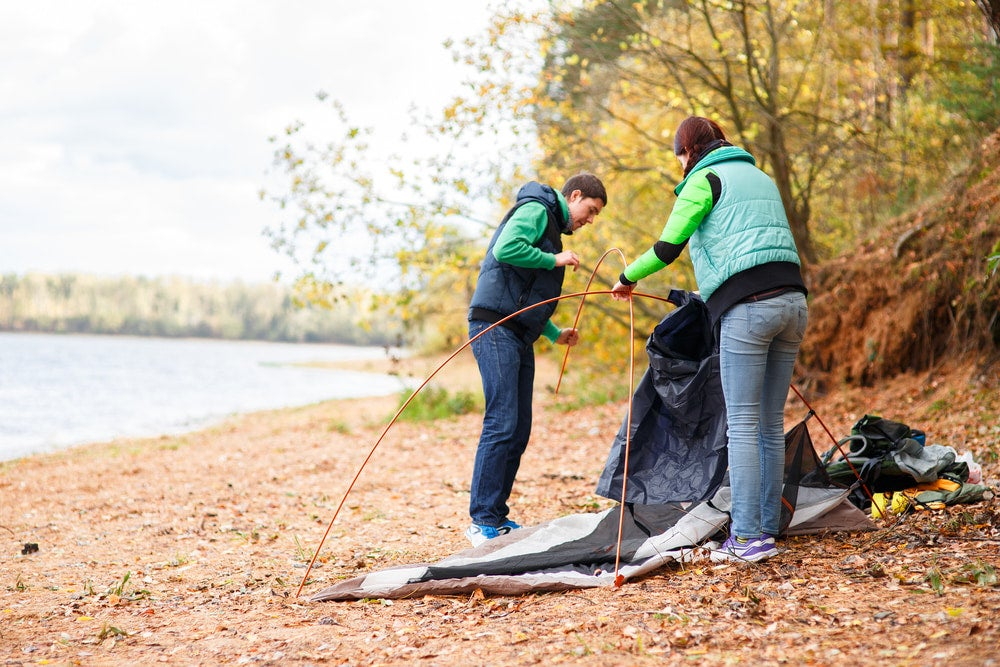 two people setting up a tent on the ground near a river