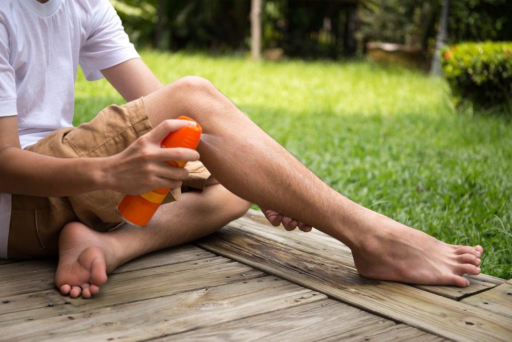 a boy spraying his leg with spray
