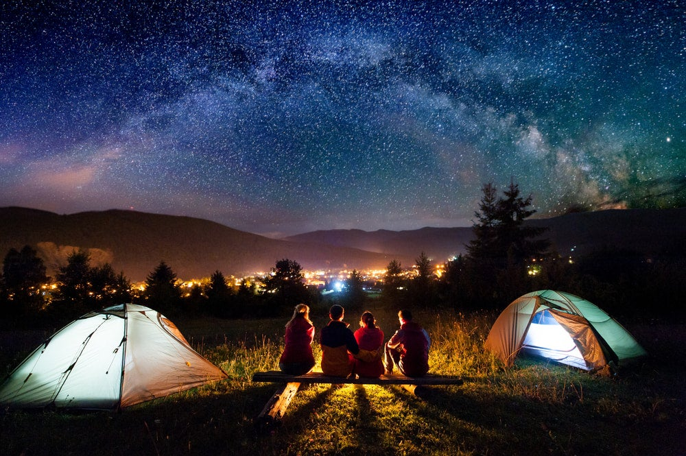 a group of campers near two tents at night