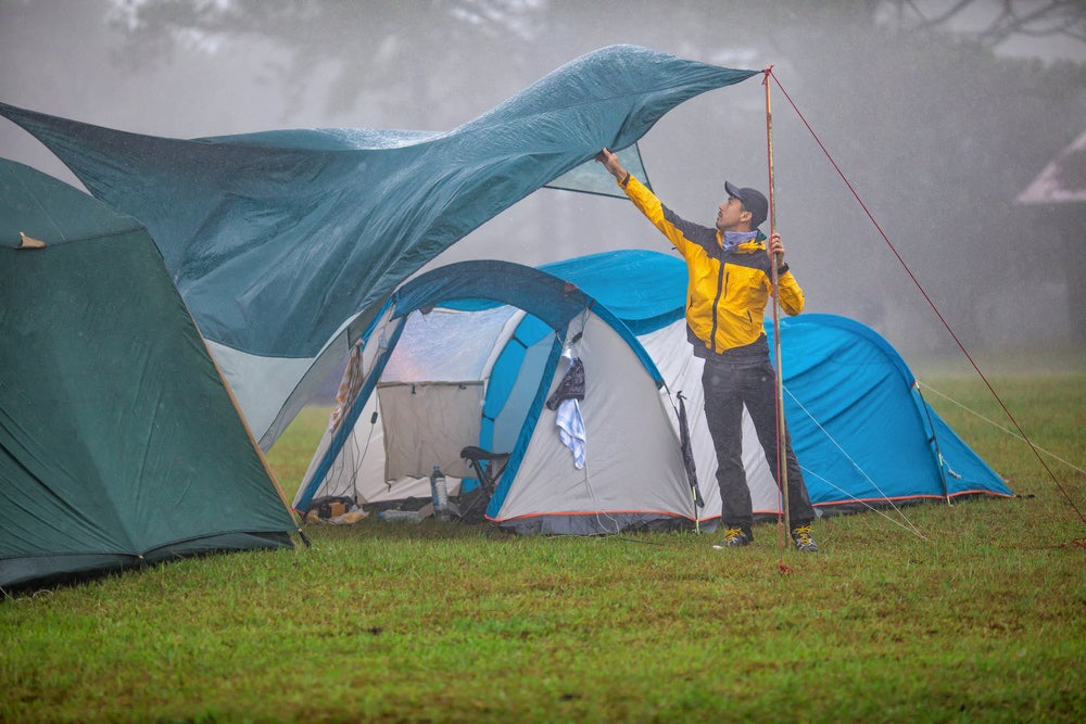 a man sets up a canopy at a campground in the rain