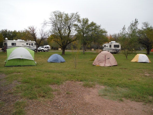 group of four tents at campsite with RVs in the background