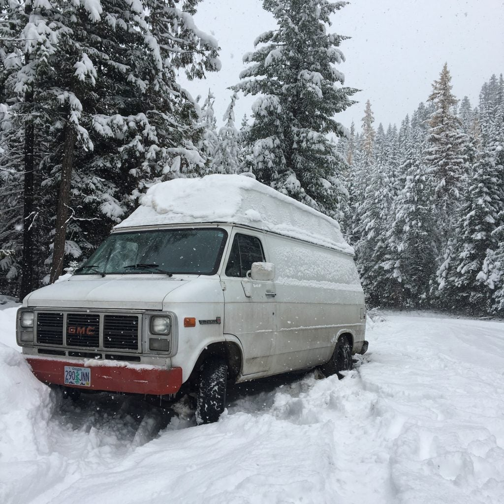GMC camper van stuck in the snow with pine trees in the background