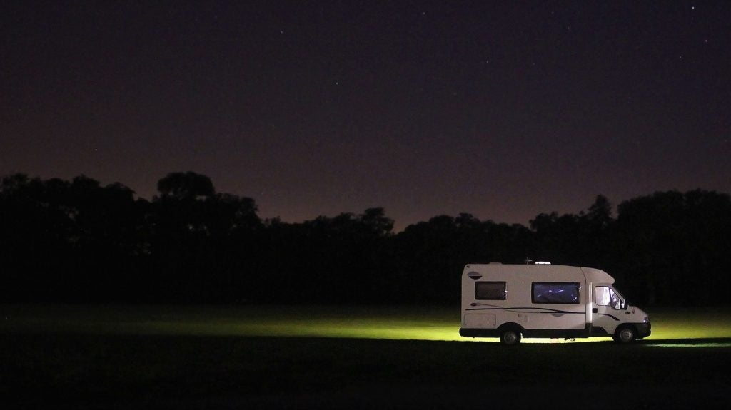 RV parked in the forest at night.