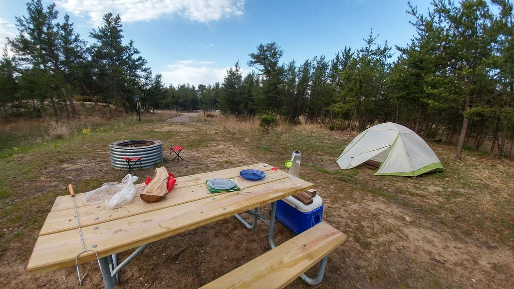 a campsite with picnic table, fire pit and tent in the woods
