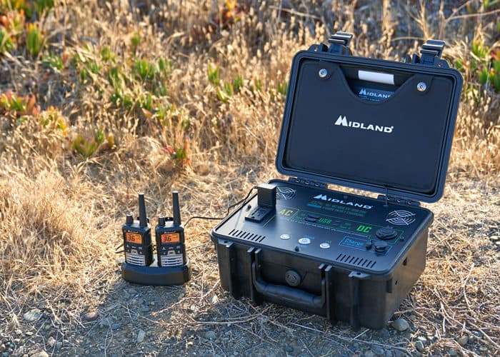 two walkie talkies next to a midland portable power station in a field of dry grass