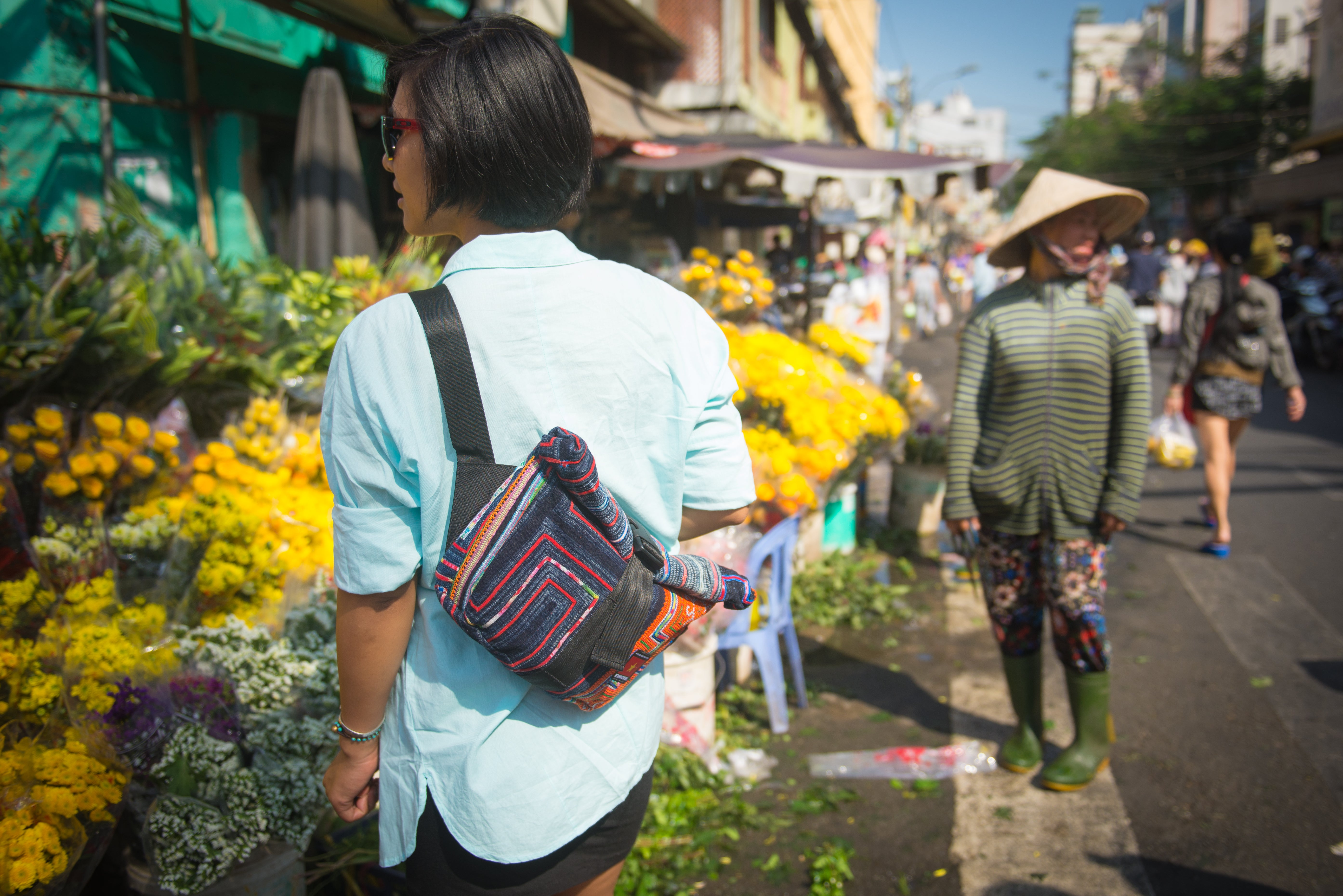 cyclo travel sling woman at market with flowers