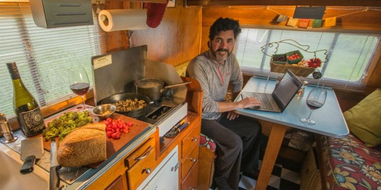 a man sitting at a table in an RV on a laptop
