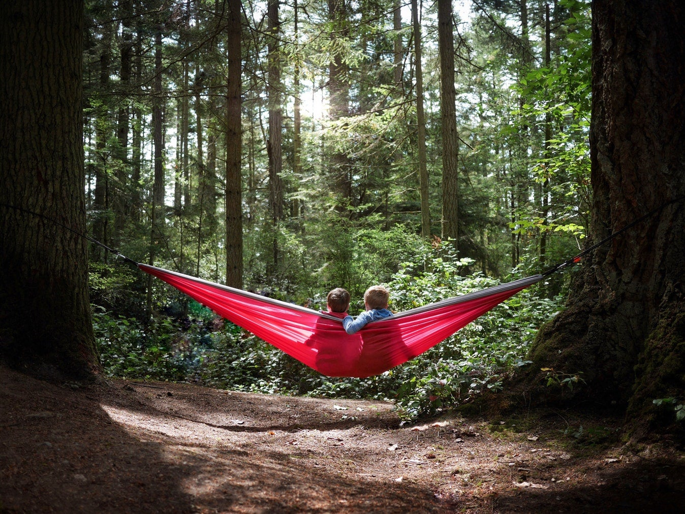 two young kids on a red hammock in deception pass state park