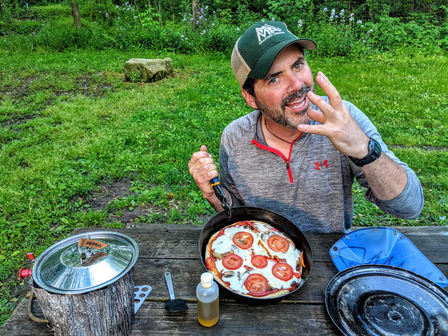 hutch demonstrating his camping kitchen hack for pizza