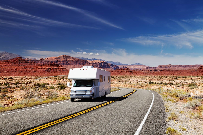 rv traveling down desert road