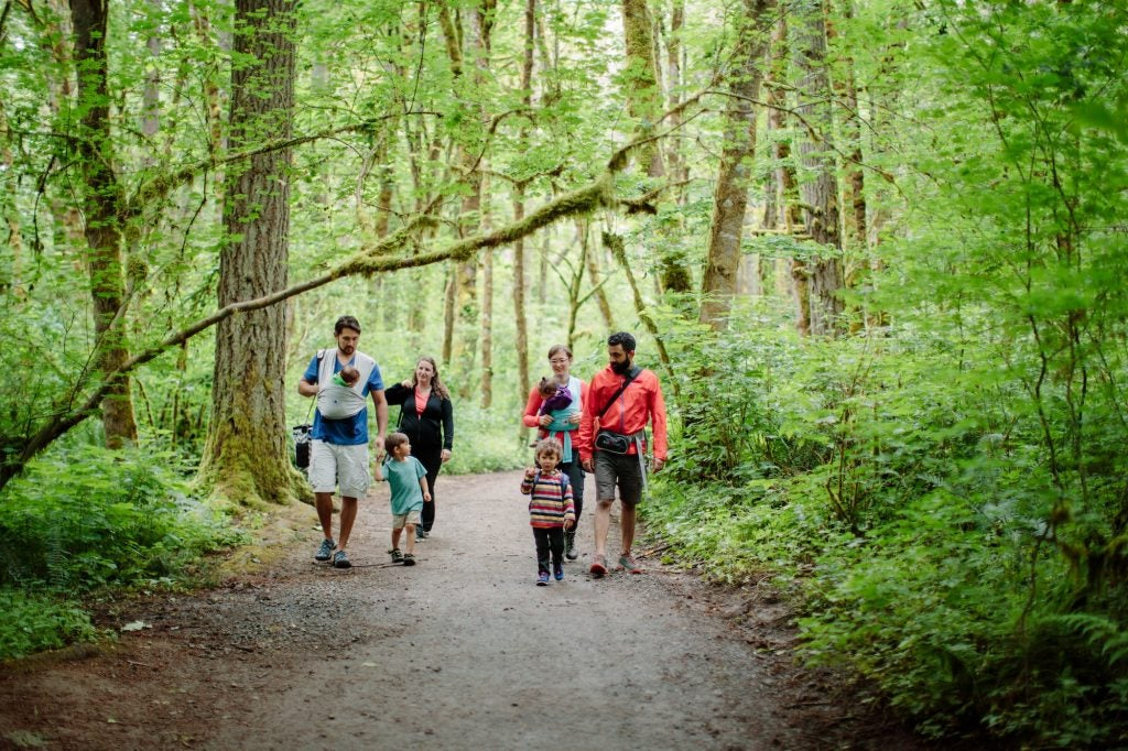 two families hike together on forest trail, via hike it baby