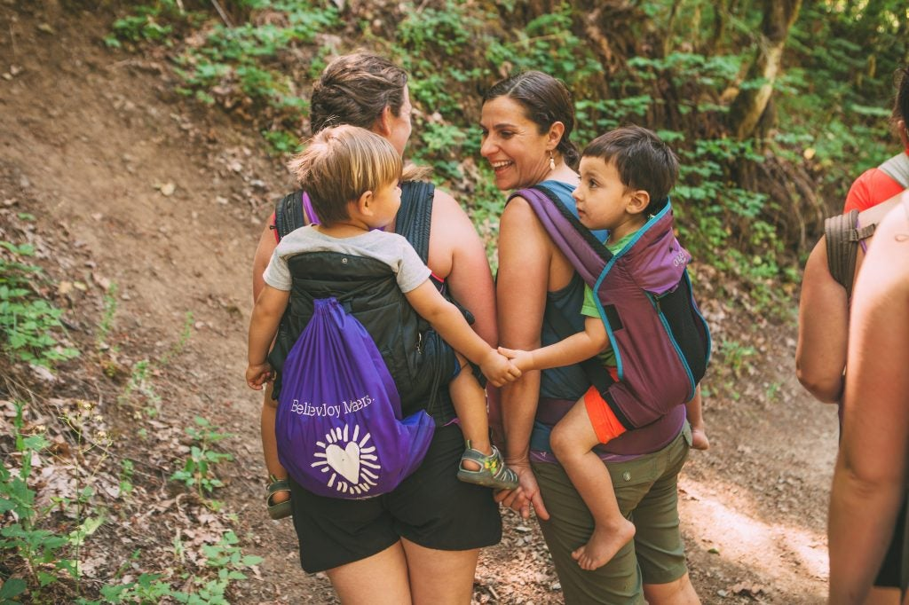 two toddlers in baby carriers holding hands on their moms, via hike it baby