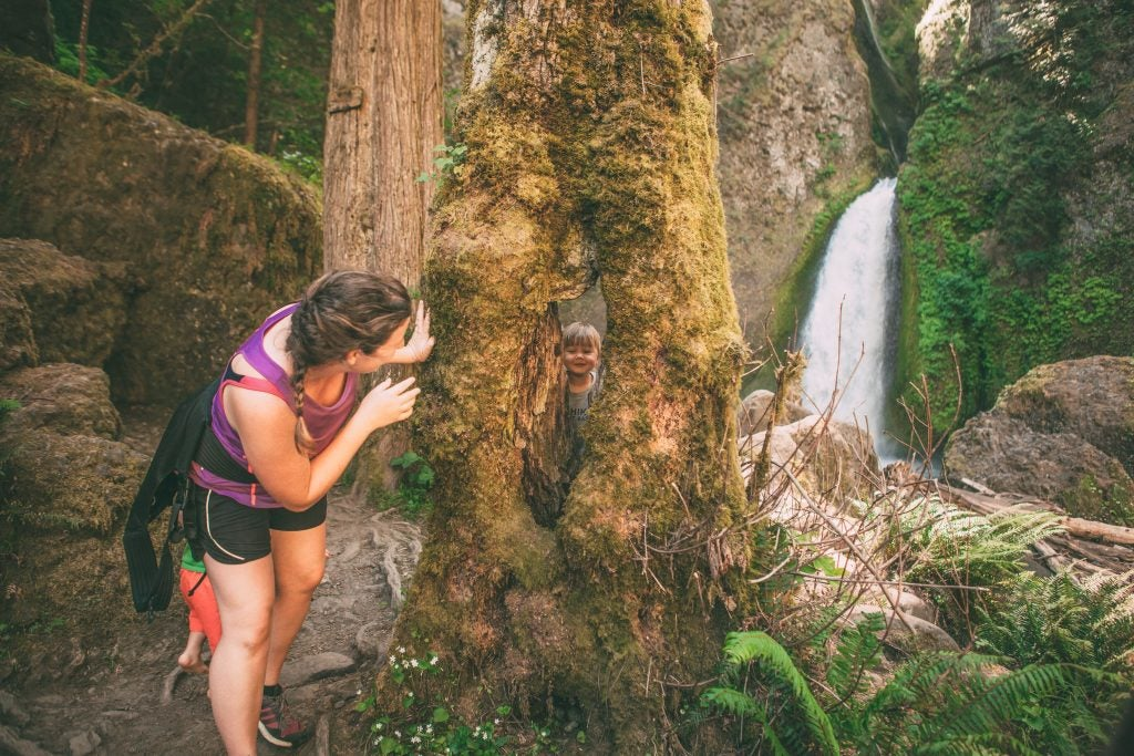 mom playing hide and seek with young son by waterfall, via hike it baby
