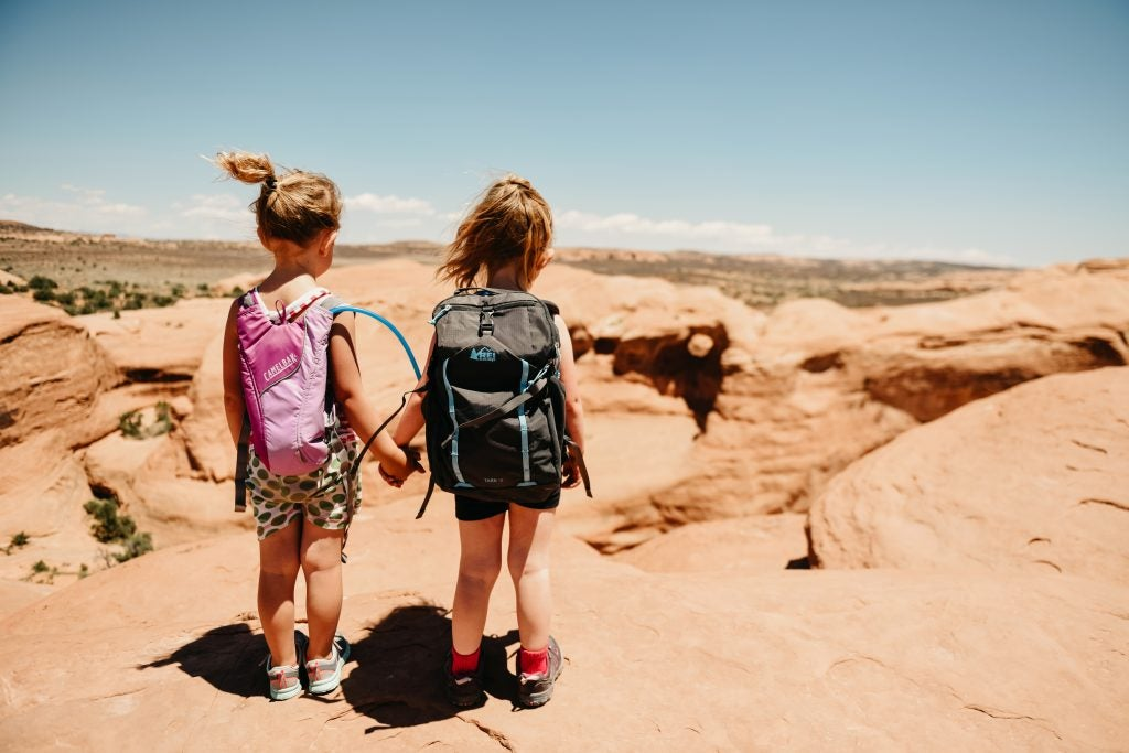 from behind: two young girls with backpacks hold hands over red rocks, via hike it baby