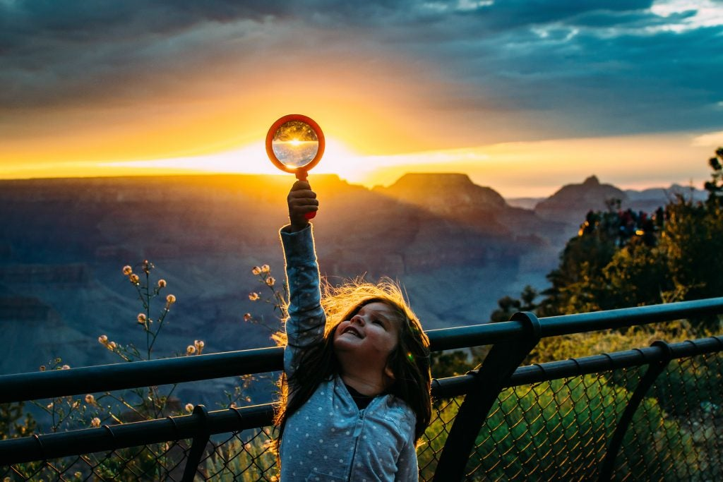 young girl holds magnifying glass up at sunset, via hike it baby