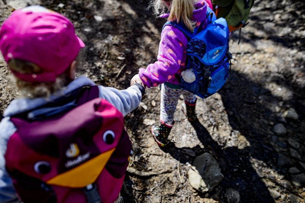 two toddler hikers holding hands on the trail, via hike it baby