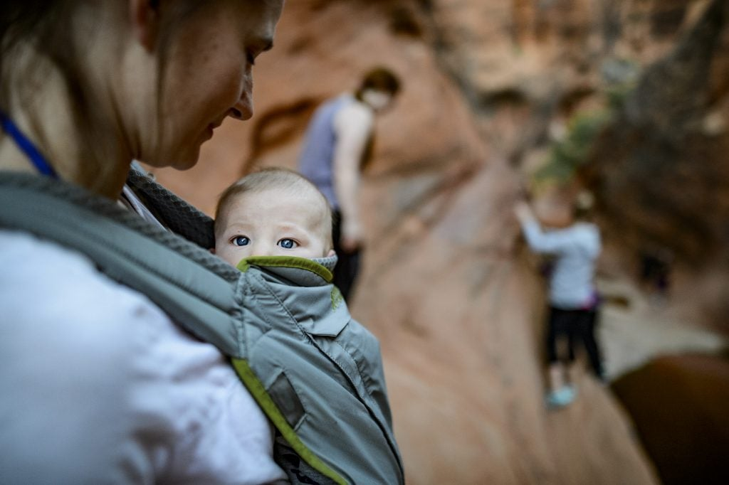 baby peeks sleepy eyes out of mom's carrier on a desert hike, via hike it baby
