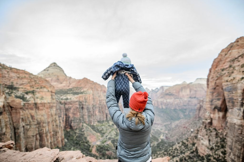 from behind: mom safely holding baby in air over canyon edge, via hike it baby