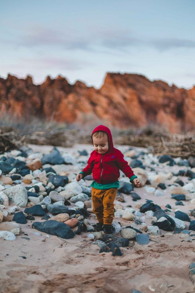 young boy in red hooded jacket walks over smooth rocks at sundown, via hike it baby