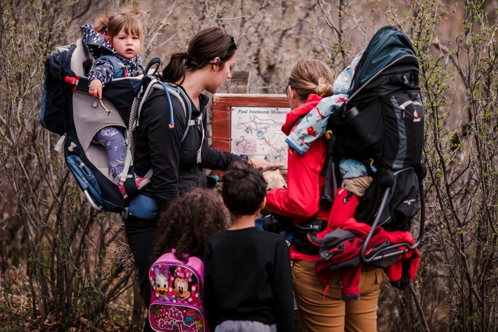 two moms use map to navigate as 4 young children watch on, via hike it baby