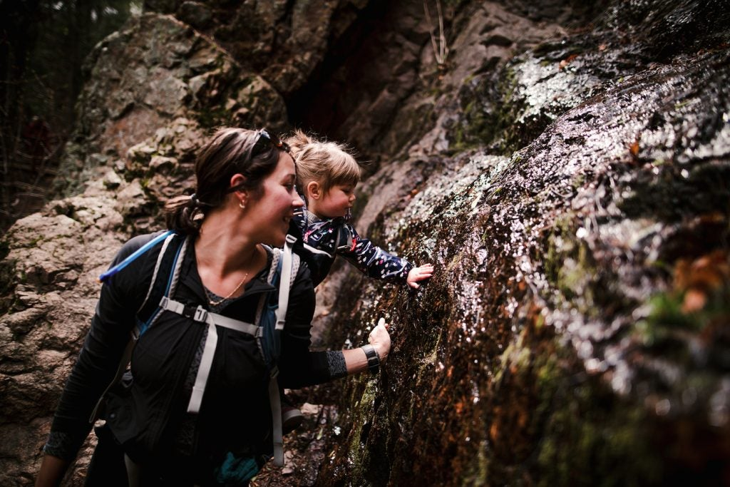 mother and daughter feeling wet rocks on hike, via hike it baby