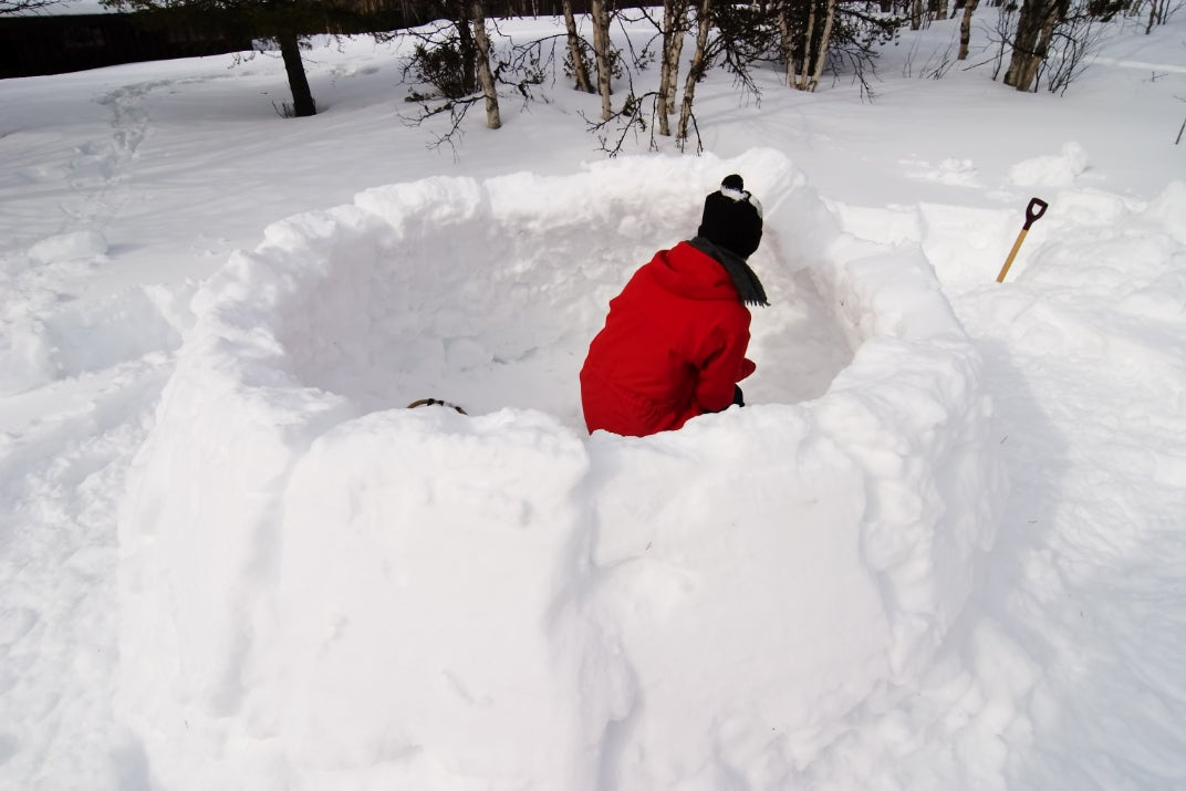 person in a red coat building the walls of an igloo in winter