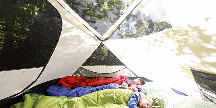 three children sleeping in tent during daytime