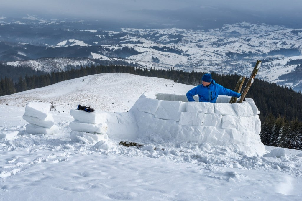a man inside a half-built igloo on a snowy hill in the mountains