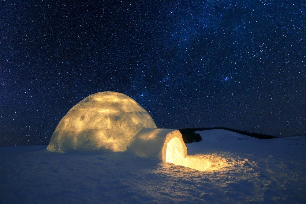 an igloo lit up at nighttime from the inside
