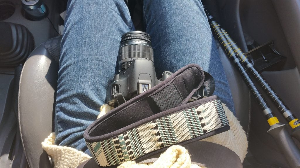 patterned camera strap in photographers lap