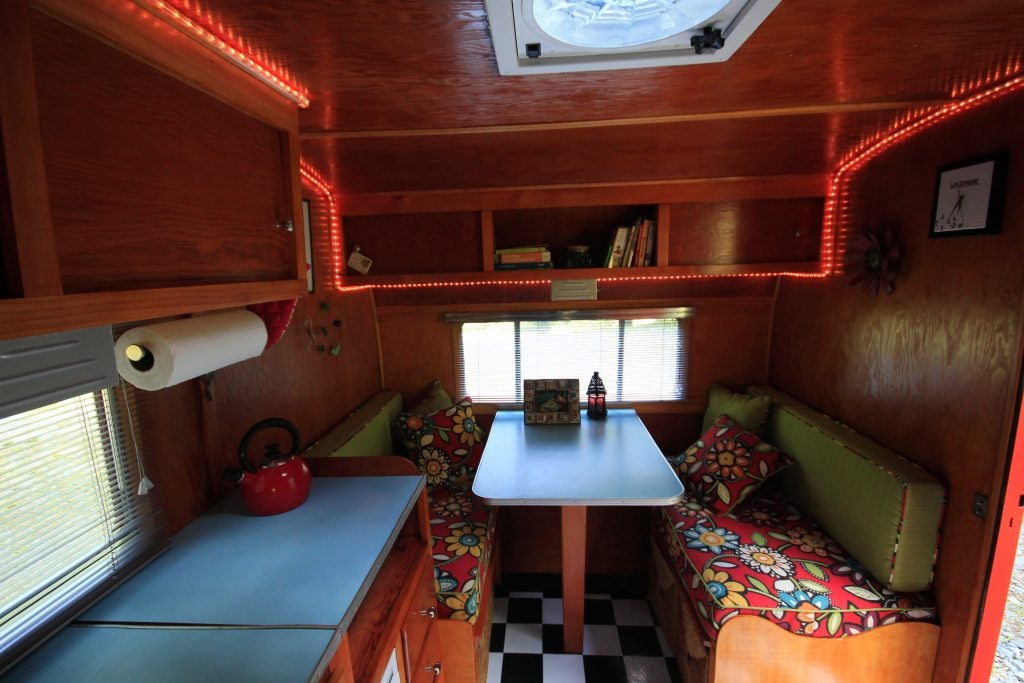 red led rope light decorates the interior of a camper trailer