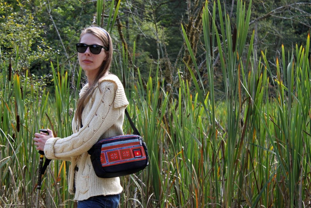 women models stylish camera bag in field of grass