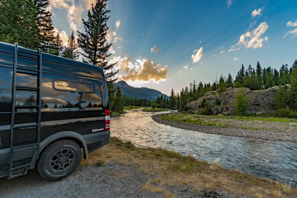 black campervan backed up to flowing river in wyoming