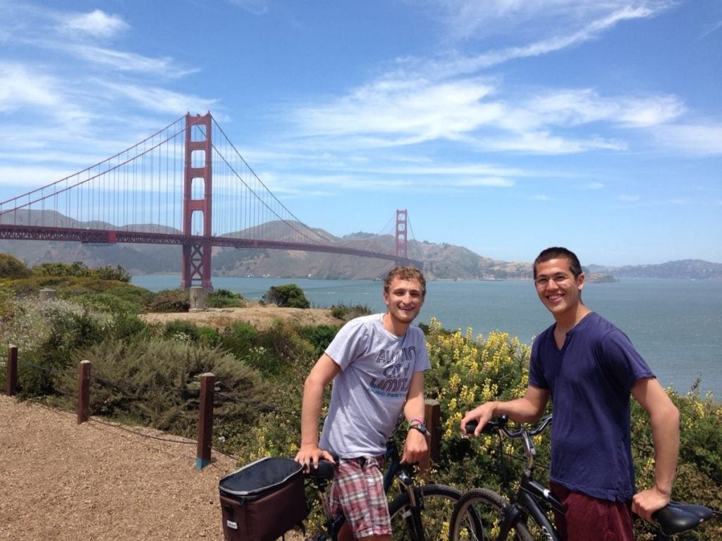 two cyclists pose in front of the golden gate bridge in san francisco