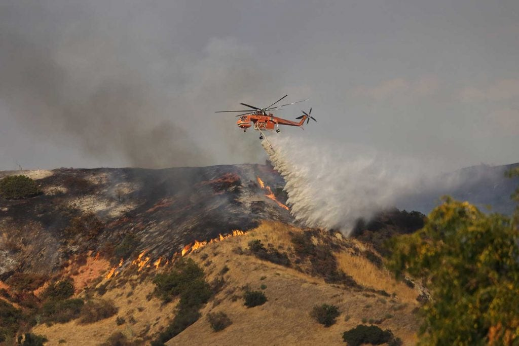 helicopter dropping fire retardant to help fire victims in california