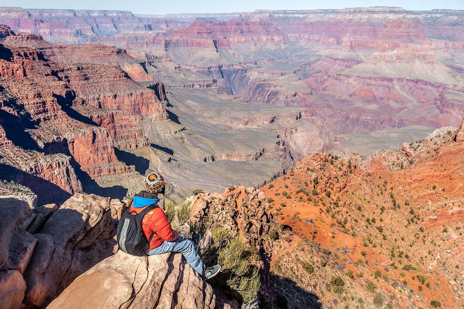 person sitting on rock overlooking the grand canyon