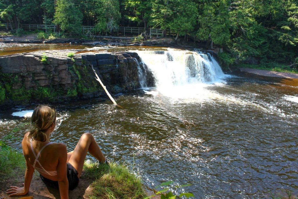 a woman rests above a cascading river in the summer