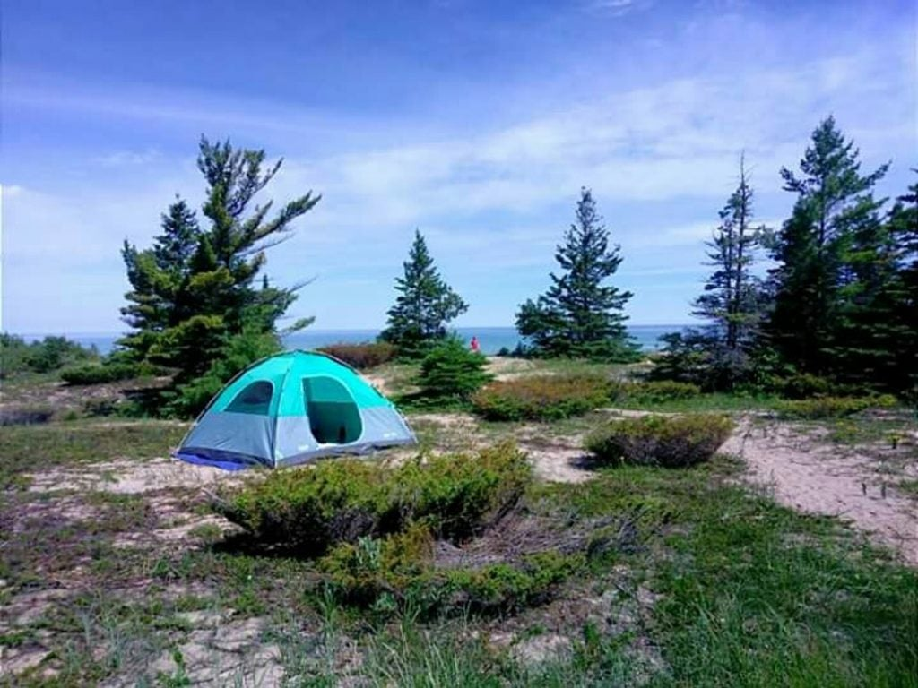a blue tent rests on a sandy, rustic campsite near lake michigan