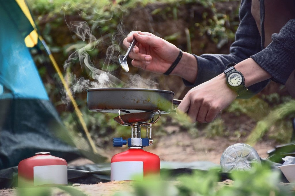 camper making breakfast hash in campsite on portable stove