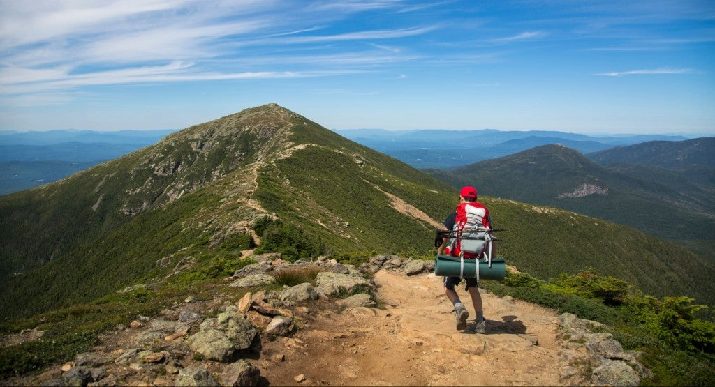 a hiker climbs a rocky mountain peak in franconia notch state park