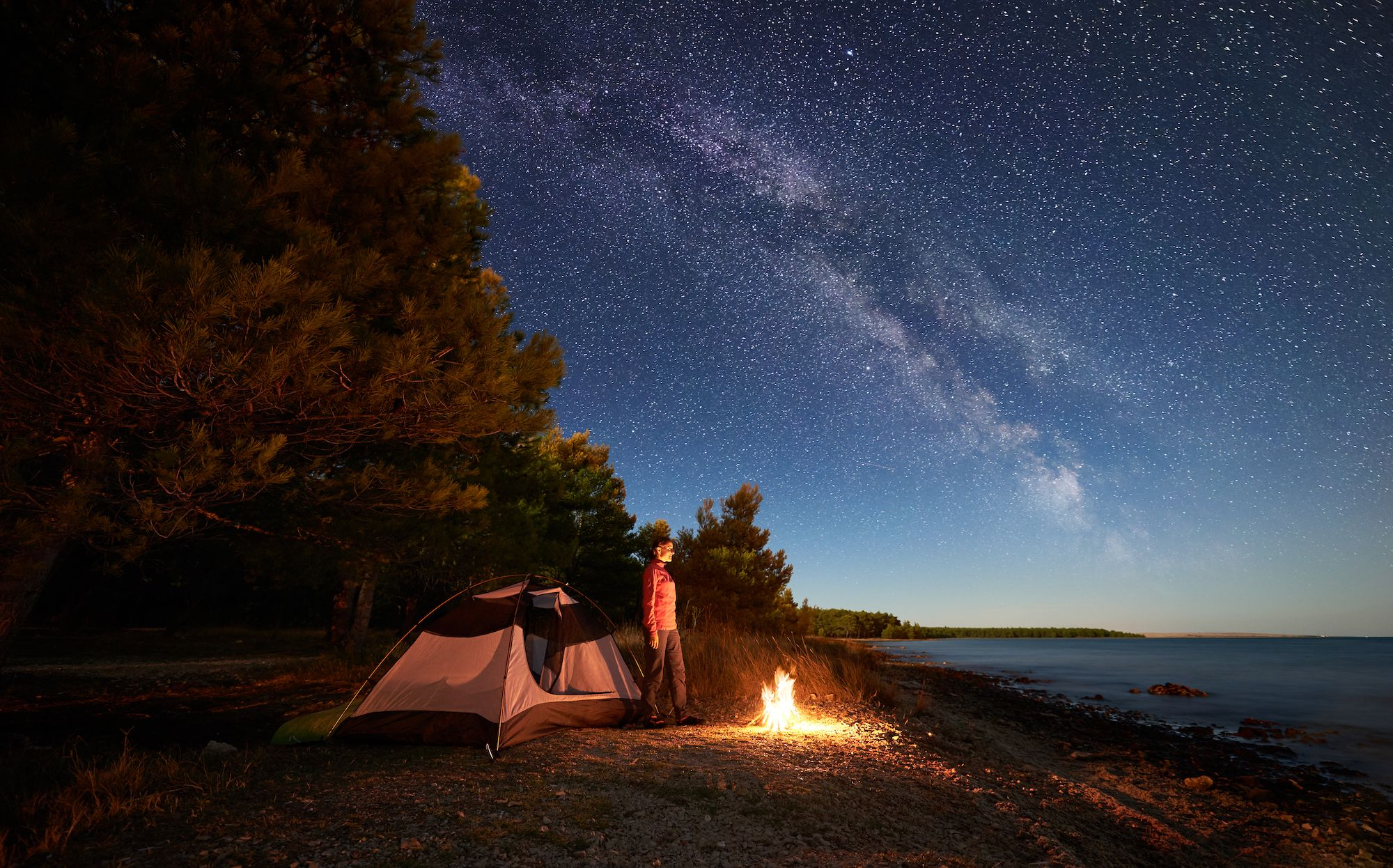 wide angle long exposure of woman standing between her tent and campfire on starry night