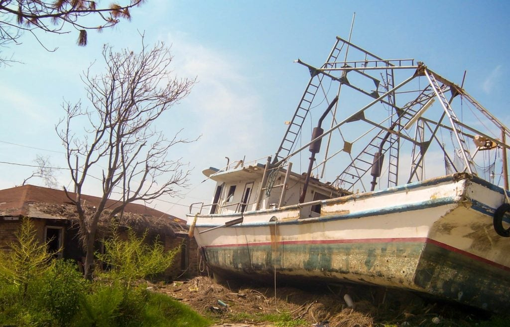 a boat abandoned on a front lawn in hurricane katrina's affected areas