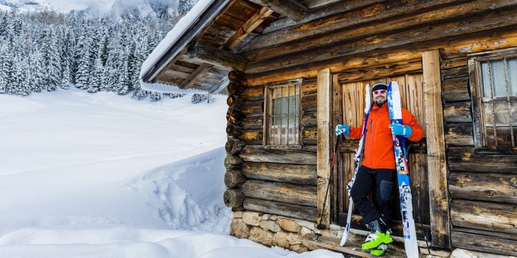 backcountry skiier standing outside his winter cabin