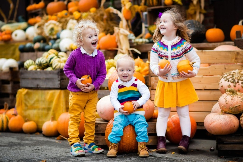 three young children pose for photos with pumpkins at a harvest festival