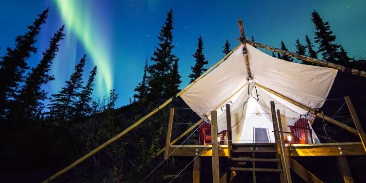 northern lights illuminate the sky above an eco-resort